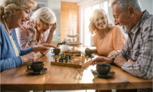 The group of seniors is playing chess board games.