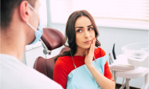 The dentist explains a temporary treatment for teeth and gums hurting.