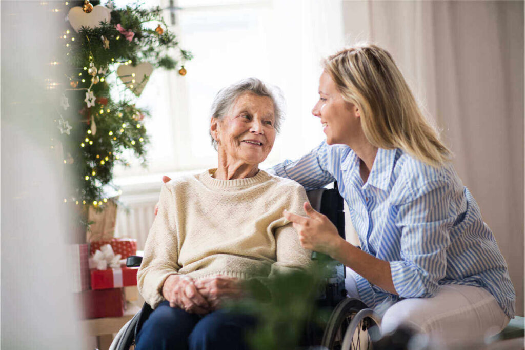 An old lady spending time with an aide in the holiday retirement home.