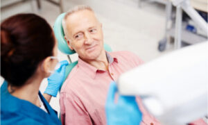 The senior patient visits a dentist to consult his dental implant issues.